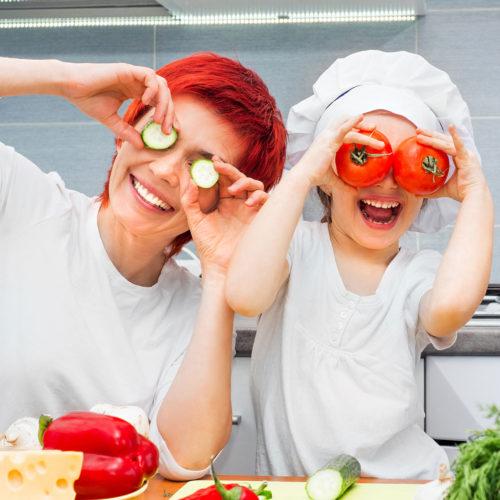 cuisinier qui joue avec des tomate et concombres bio